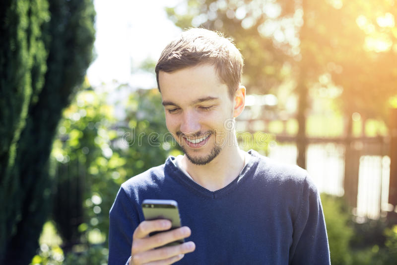 Man using smartphone. Happy man using smartphone in garden royalty free stock photos