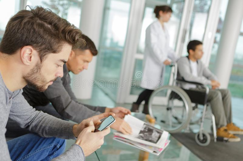 Man using smartphone in hospital waiting area royalty free stock image