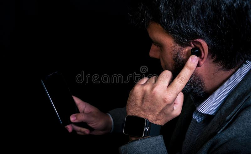 Man using smartphone and smartwatch connected to wireless earphones royalty free stock photography