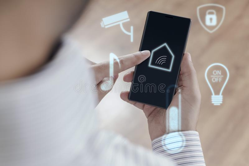 Man using smartphone to control Smart home royalty free stock photography