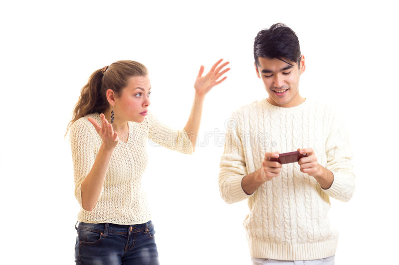 Man using smartphone and woman arguing. Young angry women with long chestnut ponytail arguing with young smiling men with dark hair in white sweater and jeans royalty free stock image
