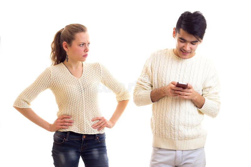 Man using smartphone and woman arguing. Young sad women with long chestnut ponytail arguing with young handsome men with dark hair in white sweater and jeans stock images