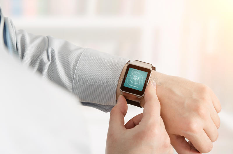 Man using smartwatch with e-mail notifier. Smartwatch hand device notify computer internet message e-mail concept royalty free stock image