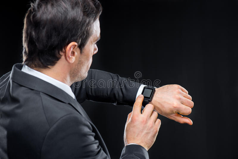 Man using smartwatch. Young man looking at his smartwatch on black royalty free stock photography