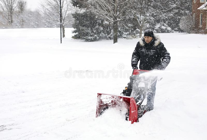 Man using a snow blowing machine, Canada royalty free stock photos