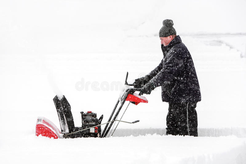 Man using a snowblower stock image