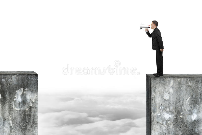 Man using speaker yelling on high concrete wall. Man using megaphone yelling on top of high concrete wall royalty free stock photo