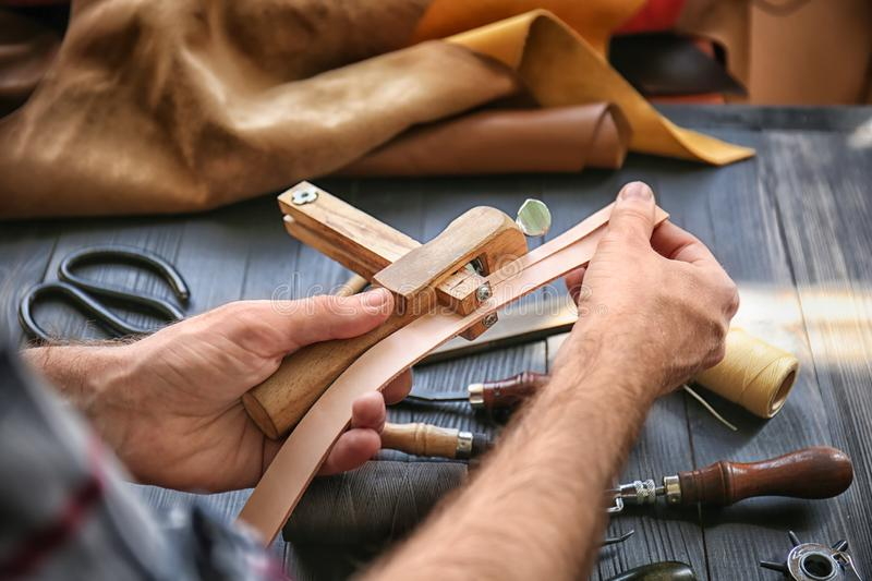 Man using stitching clamp while working with leather at factory, closeup royalty free stock photo