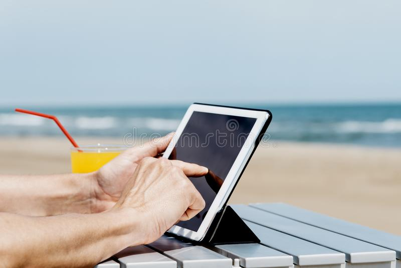 Man using a tablet on the beach stock image