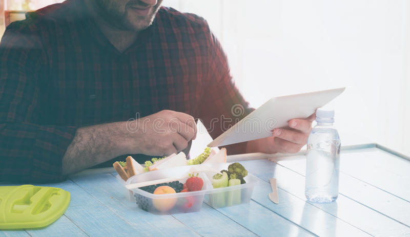 Man using tablet and eating healthy food. Concept of young business people working at home stock images
