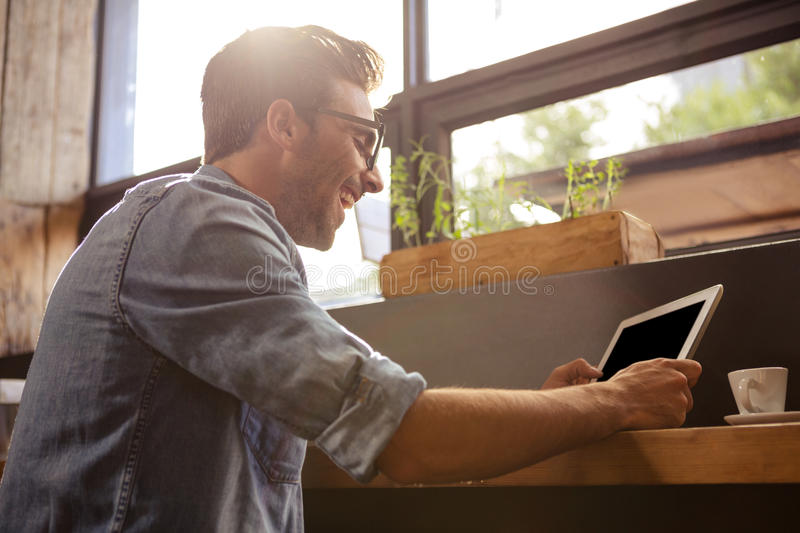Man using a tablet sitting stock photography