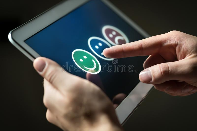 Man using tablet to give review, opinion and feedback to survey, poll or questionnaire. royalty free stock photos