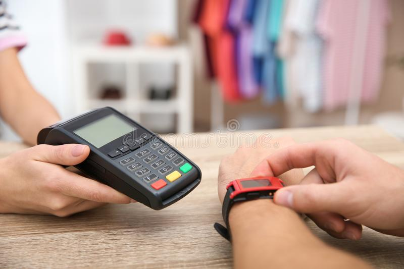 Man using terminal for contactless payment with smart watch in shop. Closeup royalty free stock images