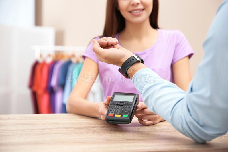 Man using terminal for contactless payment with smart watch in shop. Closeup royalty free stock image