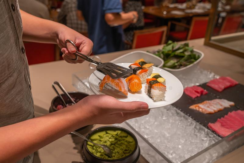 Man using tongs picking assortment of sushi in buffet meal. Man using tongs picking assortment of fresh sushi in buffet meal royalty free stock image