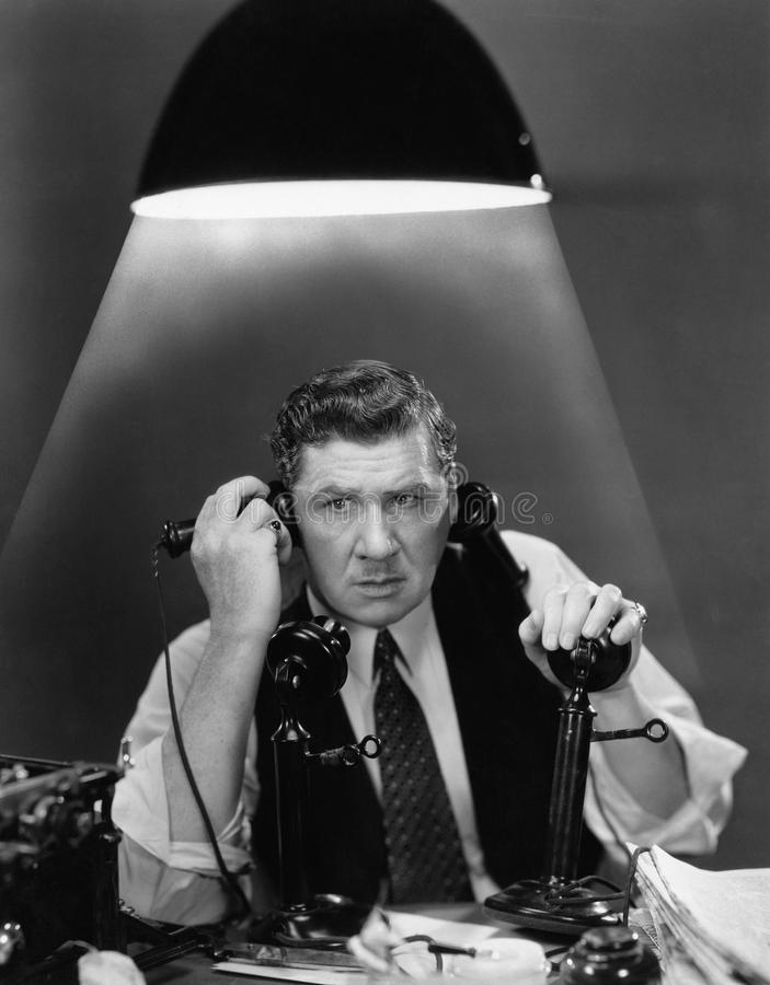 Man using two telephones. (All persons depicted are no longer living and no estate exists. Supplier grants that there will be no model release issues stock photos