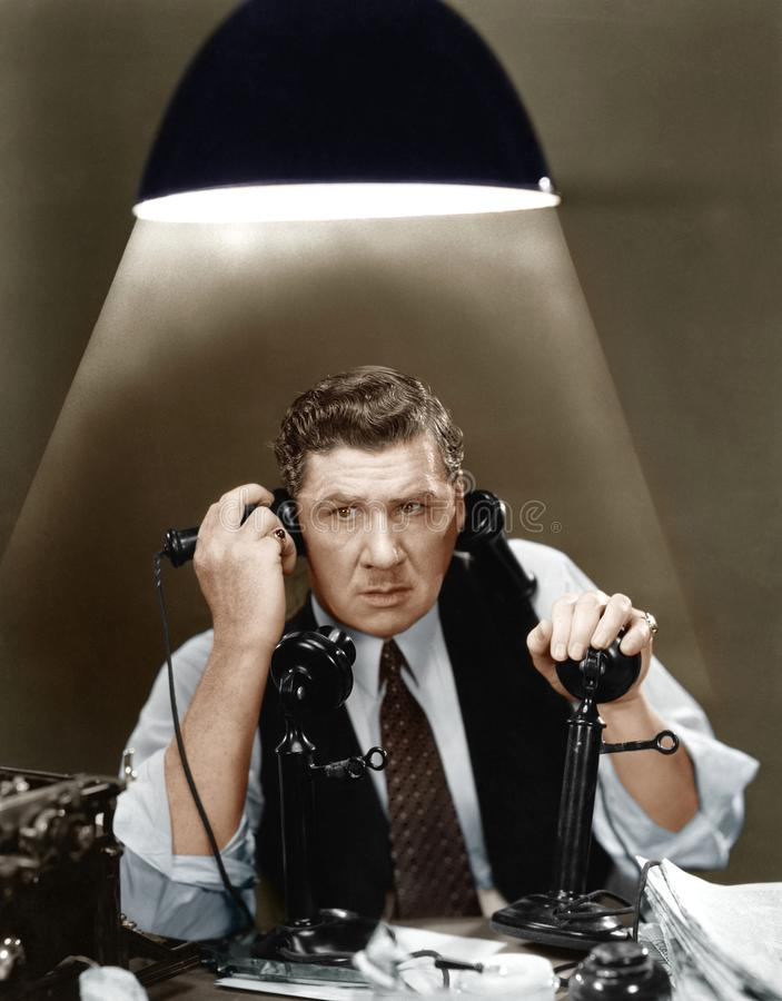 Man using two telephones. (All persons depicted are no longer living and no estate exists. Supplier grants that there will be no model release issues stock images