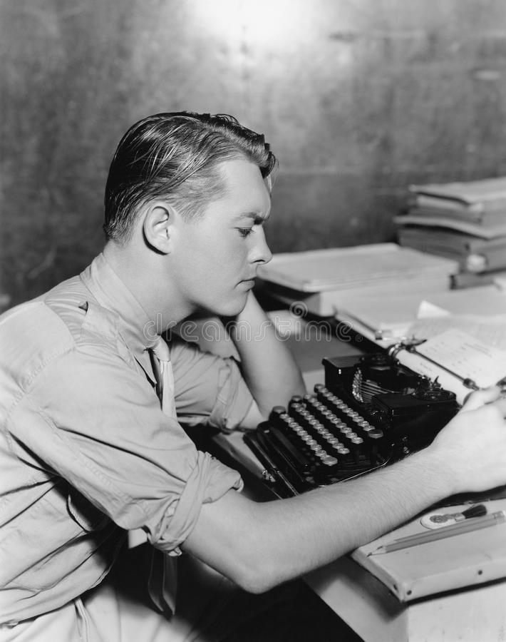 Man using typewriter. (All persons depicted are no longer living and no estate exists. Supplier grants that there will be no model release issues stock images