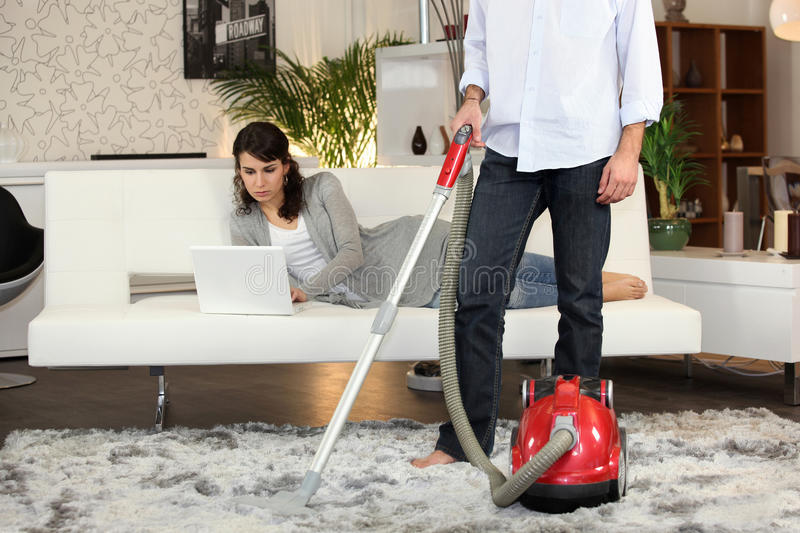 Man using a vacuum cleaner stock photo