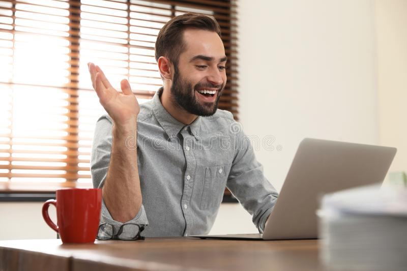 Man using video chat on laptop in office. Man using video chat on laptop in home office royalty free stock photo