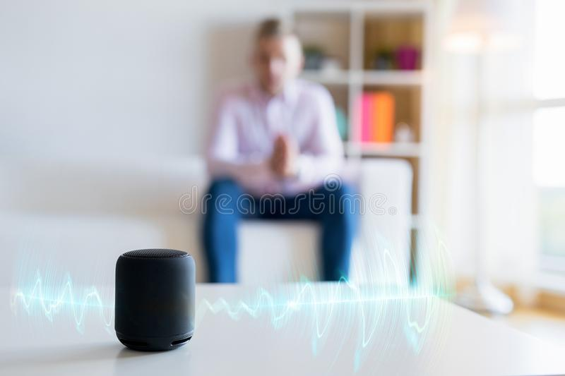 Man using virtual assistant, smart speaker at home royalty free stock photos