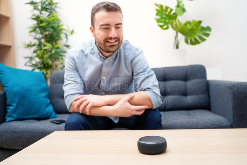 Man using virtual assistant and smart speaker at home stock image