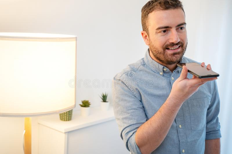 Man using virtual assistant and smart speaker at home stock images