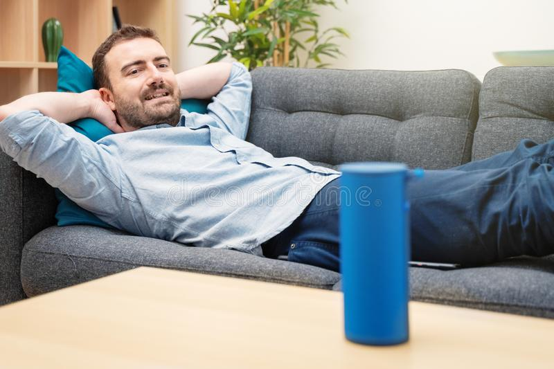 Man using virtual assistant and smart speaker at home royalty free stock image