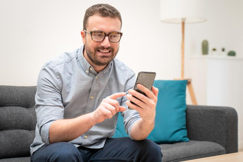 Man using virtual assistant and texting on mobile phone stock image