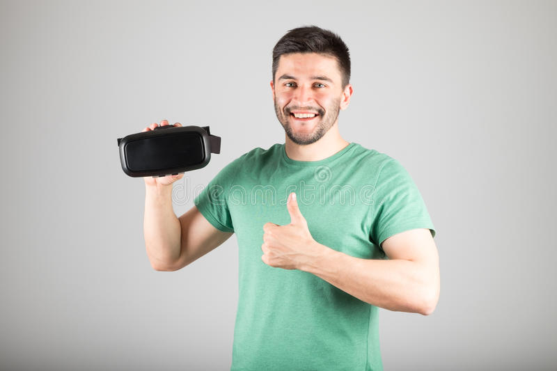 Man using virtual reality glasses. Man with virtual reality glasses showing thumb up isolated on a gray background stock photos