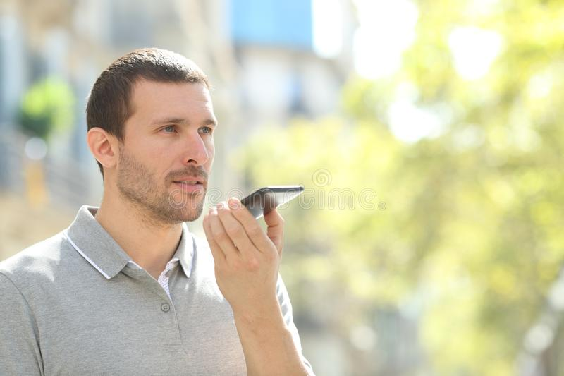 Man using voice recognition on phone in the street. Man using voice recognition on mobile phone to record messages in the street royalty free stock image