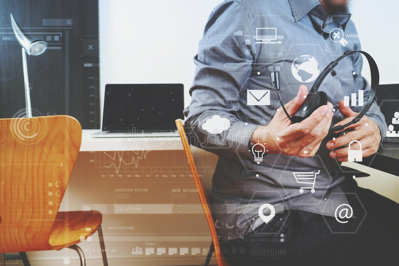 Man using VOIP headset with digital tablet and laptop computer a stock photography