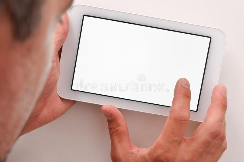 Man using white tablet with white screen on wood table stock photo