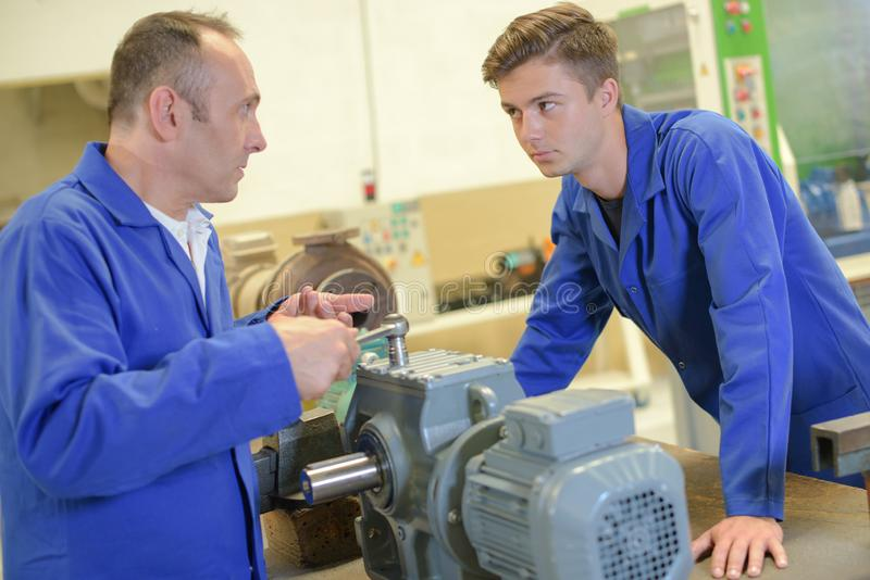 Man using wrench on machine apprentice watching stock photos