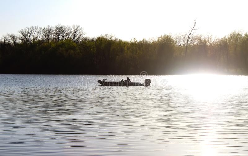 Man ut i fiskebåt på floden i tidig dimmig morgon med rök från utombordsmotorvisning mot träd royaltyfria bilder