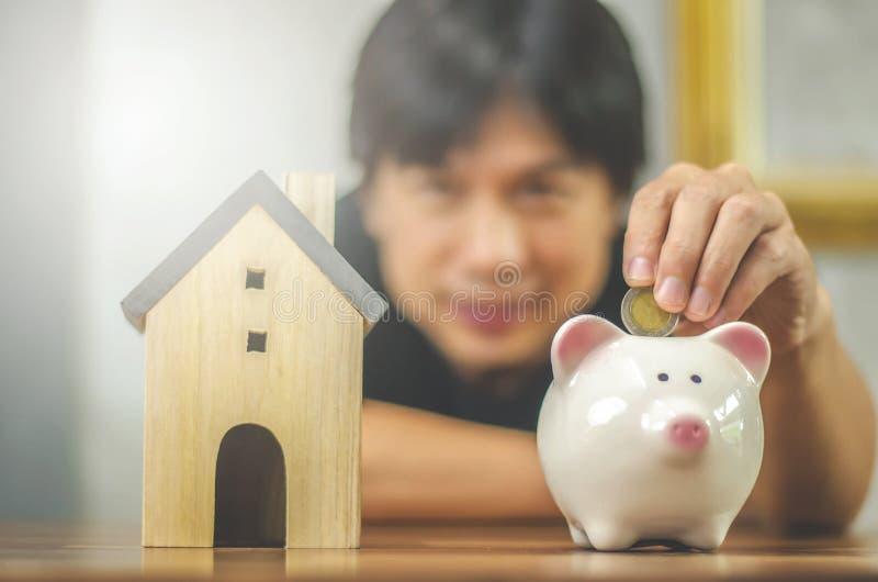 Man ut ur fokusen som sätter in myntet i spargrisen av en trätabell: fastigheten egenskapsinvesteringen, hus intecknar, arkivfoto