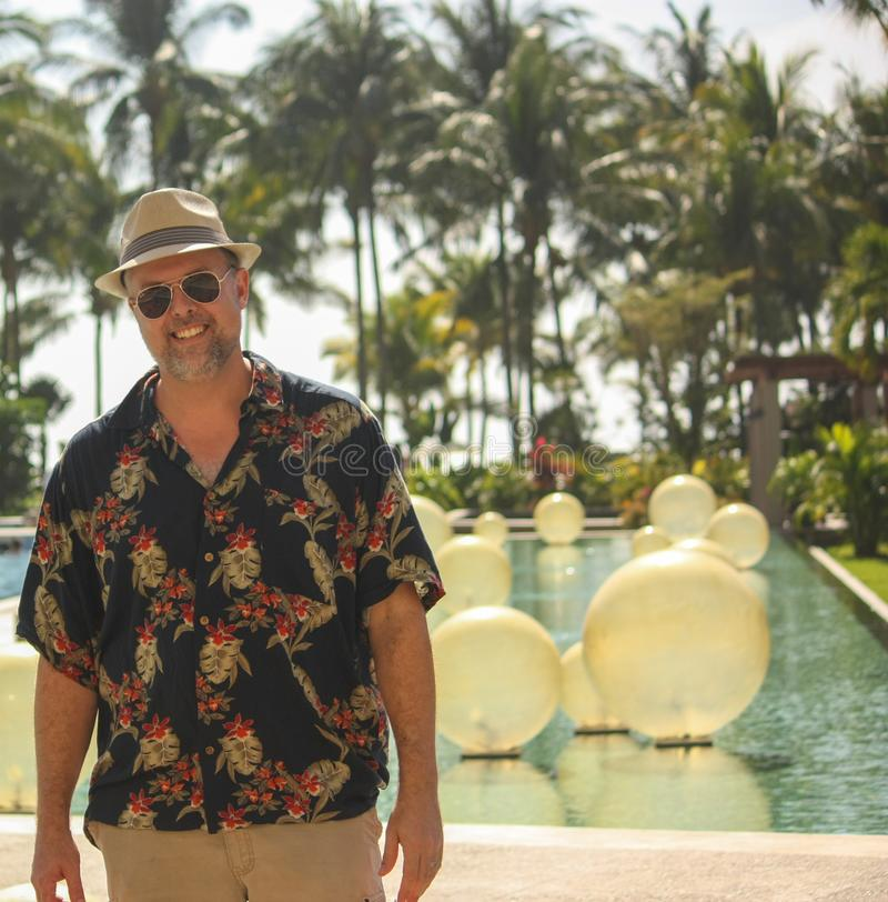 Man on Vacation: Enjoying life in Mexico. Attractive middle aged man wearing a beach hat, sunglasses, and Hawaiian shirt soaking up the beach and pool life in royalty free stock photo