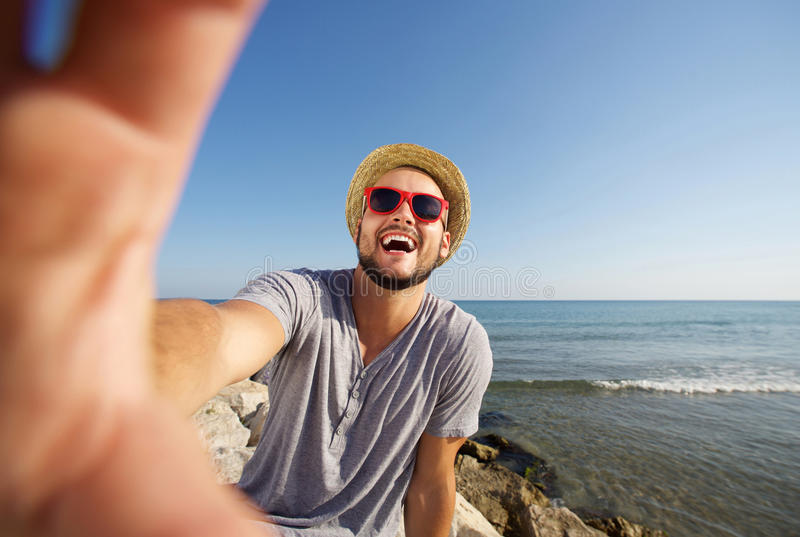 Man on vacation laughing at the beach taking selfie stock images