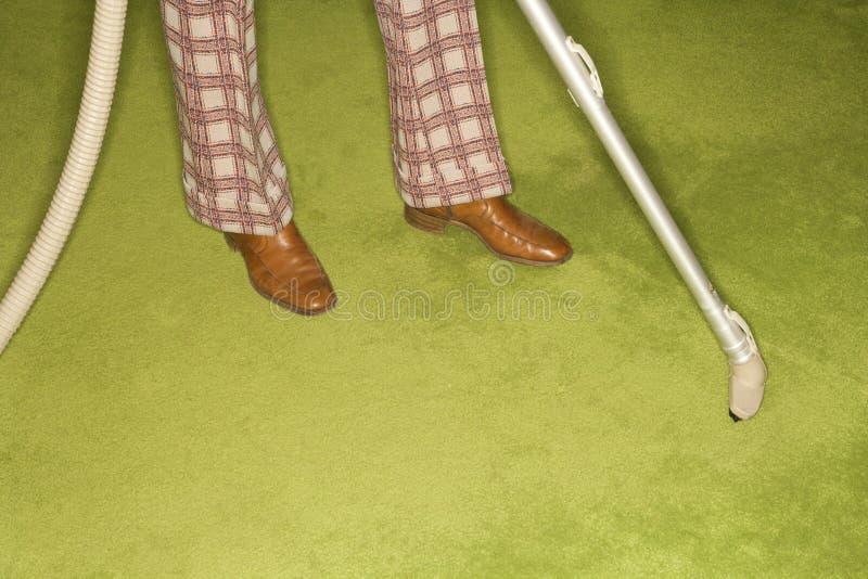 Man vacuuming rug. royalty free stock photos