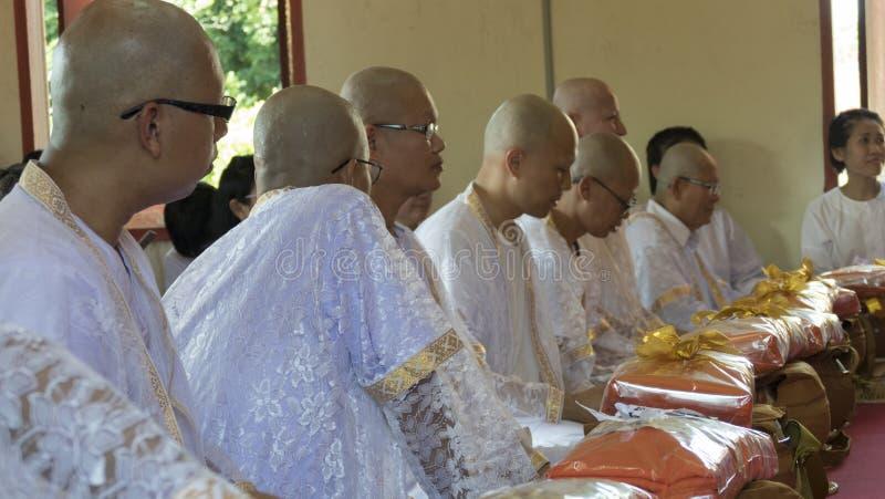 Man vem ska bli buddhismmunksammanträde och den väntande på ordinaen arkivbild