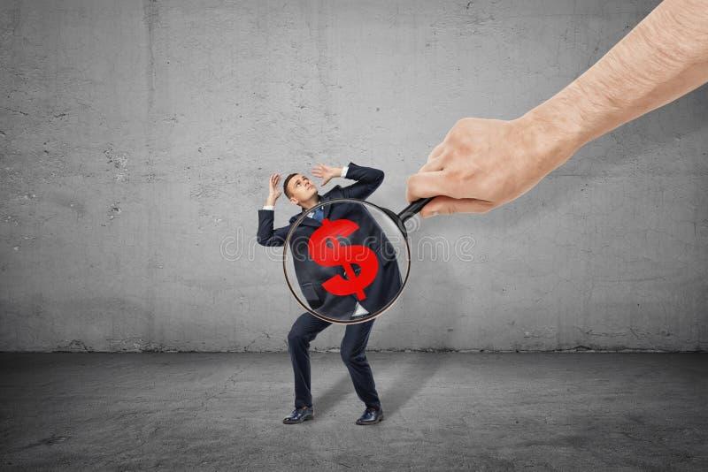Man vergrootglas van de handholding bij de maag van weinig zakenman met rood dollarsymbool op het royalty-vrije stock fotografie