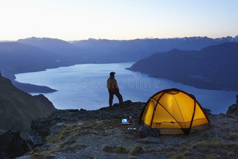 Man vid sjön och tält på skymning royaltyfri bild