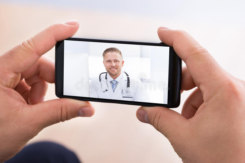 Man video chatting with doctor stock images