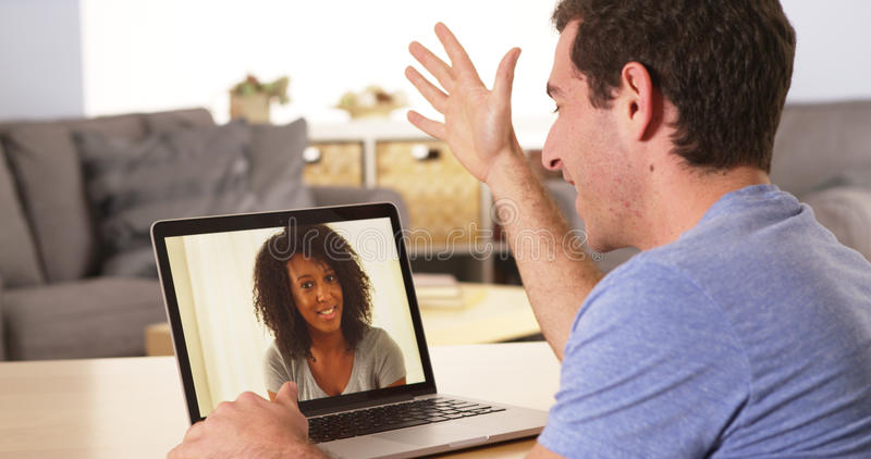 Man video chatting with a woman online royalty free stock image