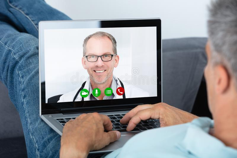 Man Videoconferencing With Doctor On Laptop royalty free stock photography