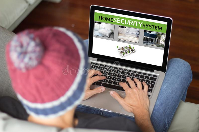 Young man on the sofa viewing security cam software royalty free stock photography