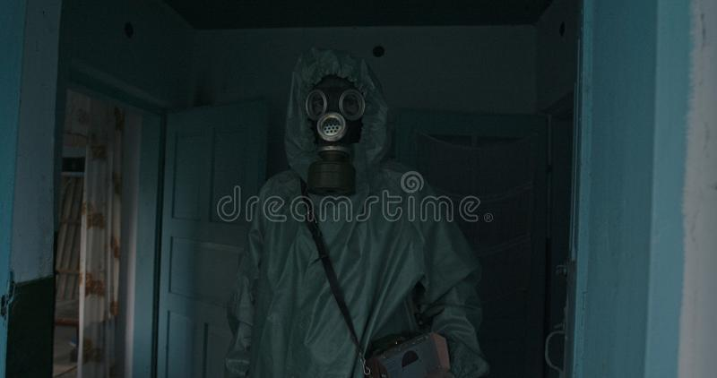 Man in Vintage WWII Hazmat suit and gas mask standing in the doorway of a house. The dosimeter in the Chernobyl zone stock photography