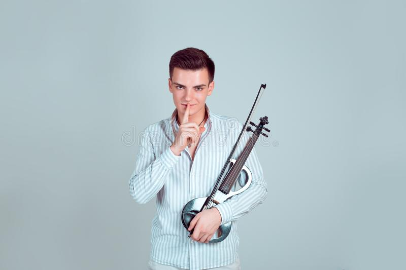 Man with violin covering mouth in silence stock photo