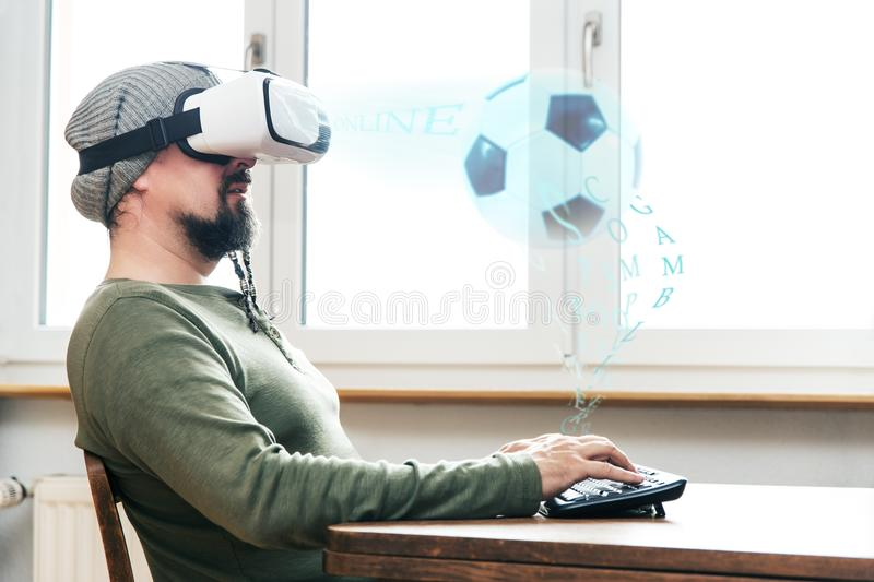 Man with vr glasses. Man with virtual reality glasses is sitting on a table, concept soccer game, gambling or streaming royalty free stock photos