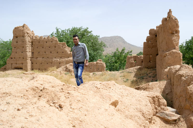 Man visiting a historical ruins site. In Morocco old houses and kasbahs like this are made out of soil (dirt). Some people still prefer this material to modern royalty free stock image